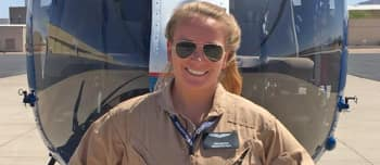 Pilot Leah Murphy stands in front of a helicopter, smiling