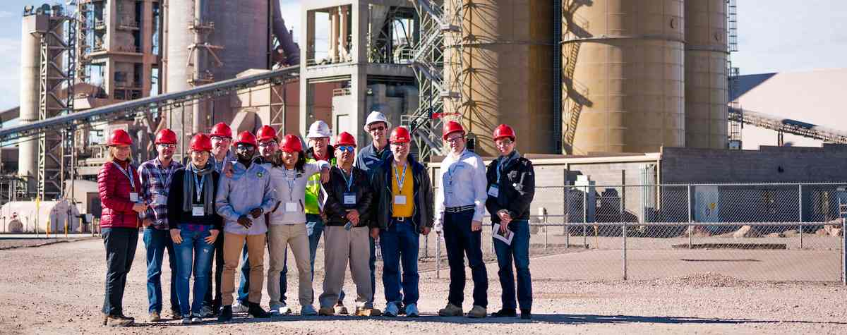 Students stand outside a cement manufacturing plant during an on site business consultation