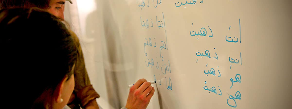 Students learn to write Arabic on a white board in classroom