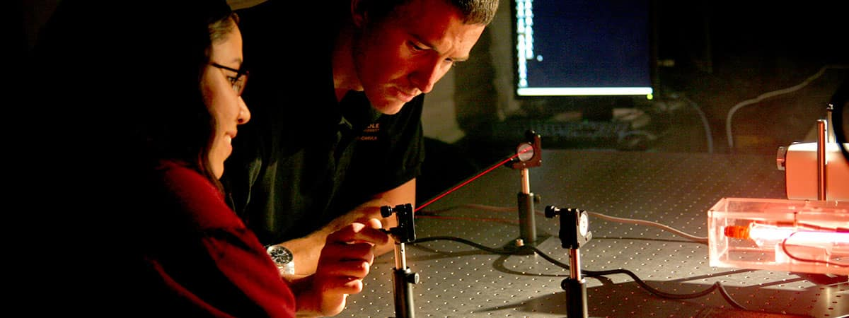 Two students experiment with laser light detection equipment in a laboratory
