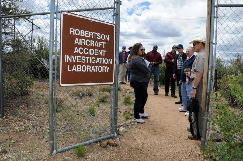 Students stand inside a fence with a sign that reads Robertson Aircraft Accident Investigation Laboratory.