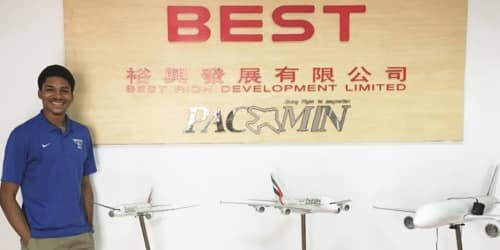 Study Abroad student stands in front of a sign with Chinese characters beside three model commercial aircraft