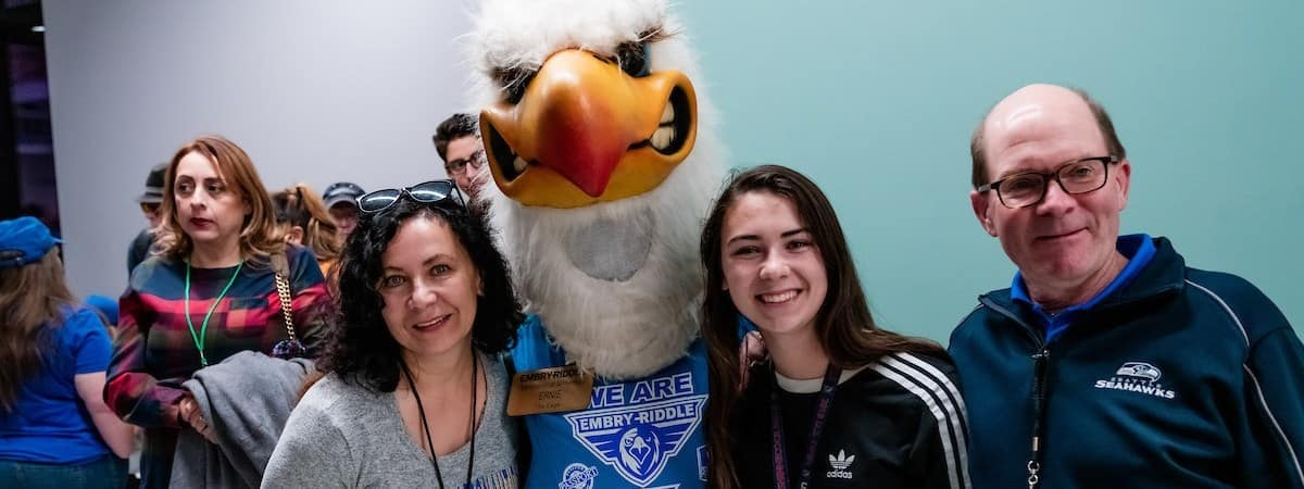 A student and their parents meeting Ernie the Eagle