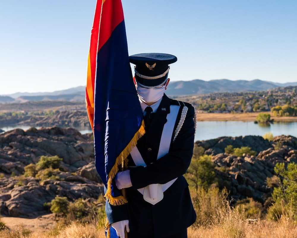 A masked ROTC cadet stands with the Arizona flag in front of Willow Lake