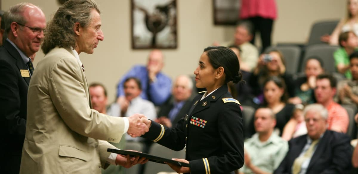 An award is presented to a soldier on stage in the Davis Learning Center auditorium