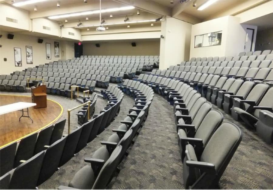DLC Auditorium, featuring stadium seating, stage, retractable large screen for projector demonstrations