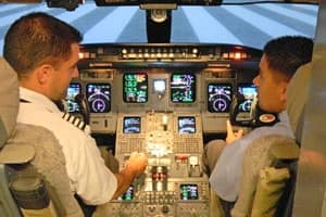A student and instructor sit in the simulated cockpit of a Level D CRJ-700 Regional Jet Simulator at Embry-Riddle Aeronautical University's Prescott campus