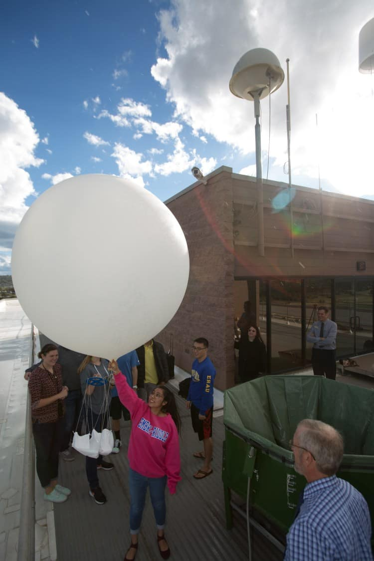 A student launches a weather balloon from the rooftop observation deck