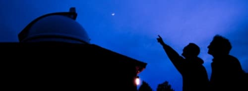 An Astronomy instructor points out particular stars and orbital bodies of interest to a student looking up at the night sky outside of campus' observatory
