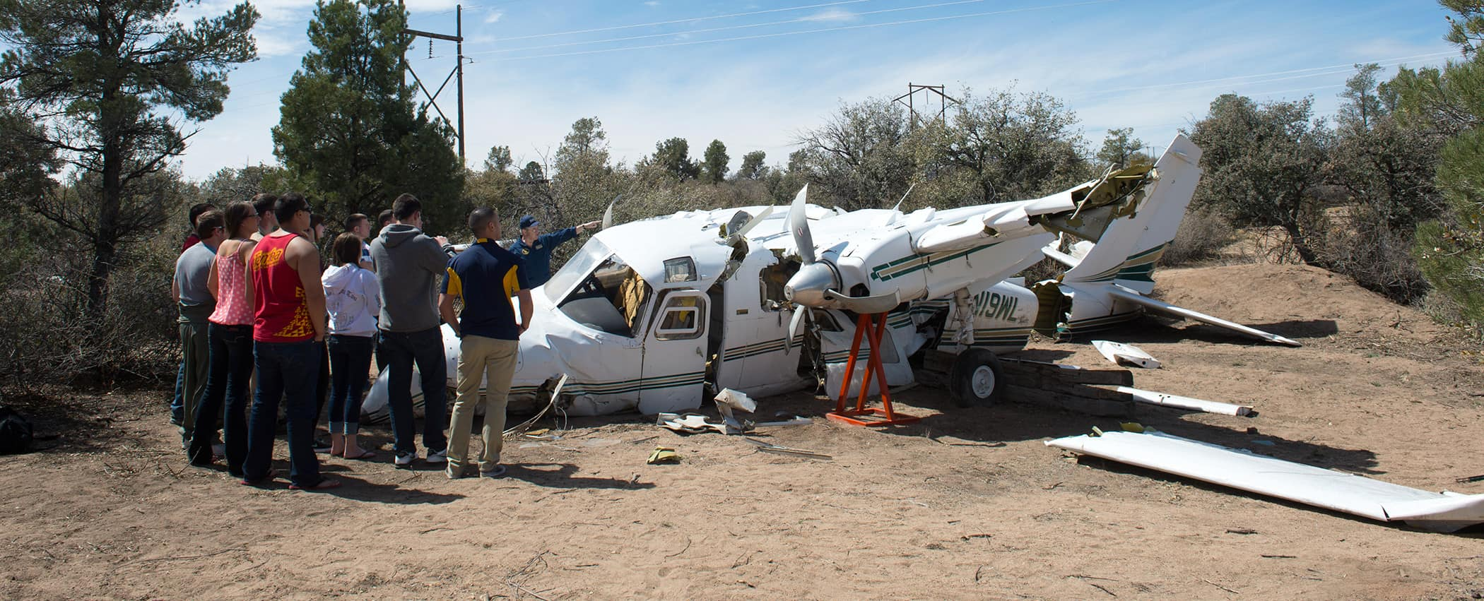 A group of students gather near a crashed plane